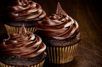 Three chocolate cupcakes over a dark wooden background
