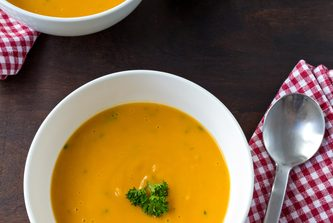 Colorful creamy soup made of pumpkin, sweet potato and coconut milk. Decorated with parsley. Two servings